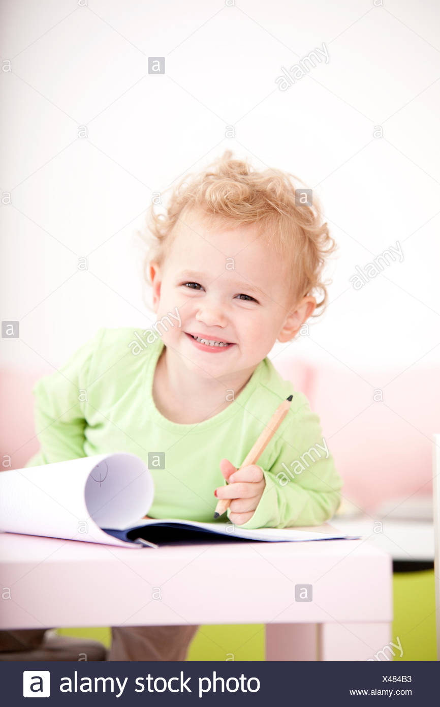 Portrait of grinning little blond girl with coloured pencil - Stock Image