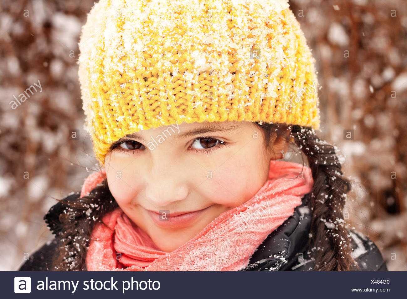 Pretty little girl (6-7) in braids and hat, smiling during snow fall - Stock Image