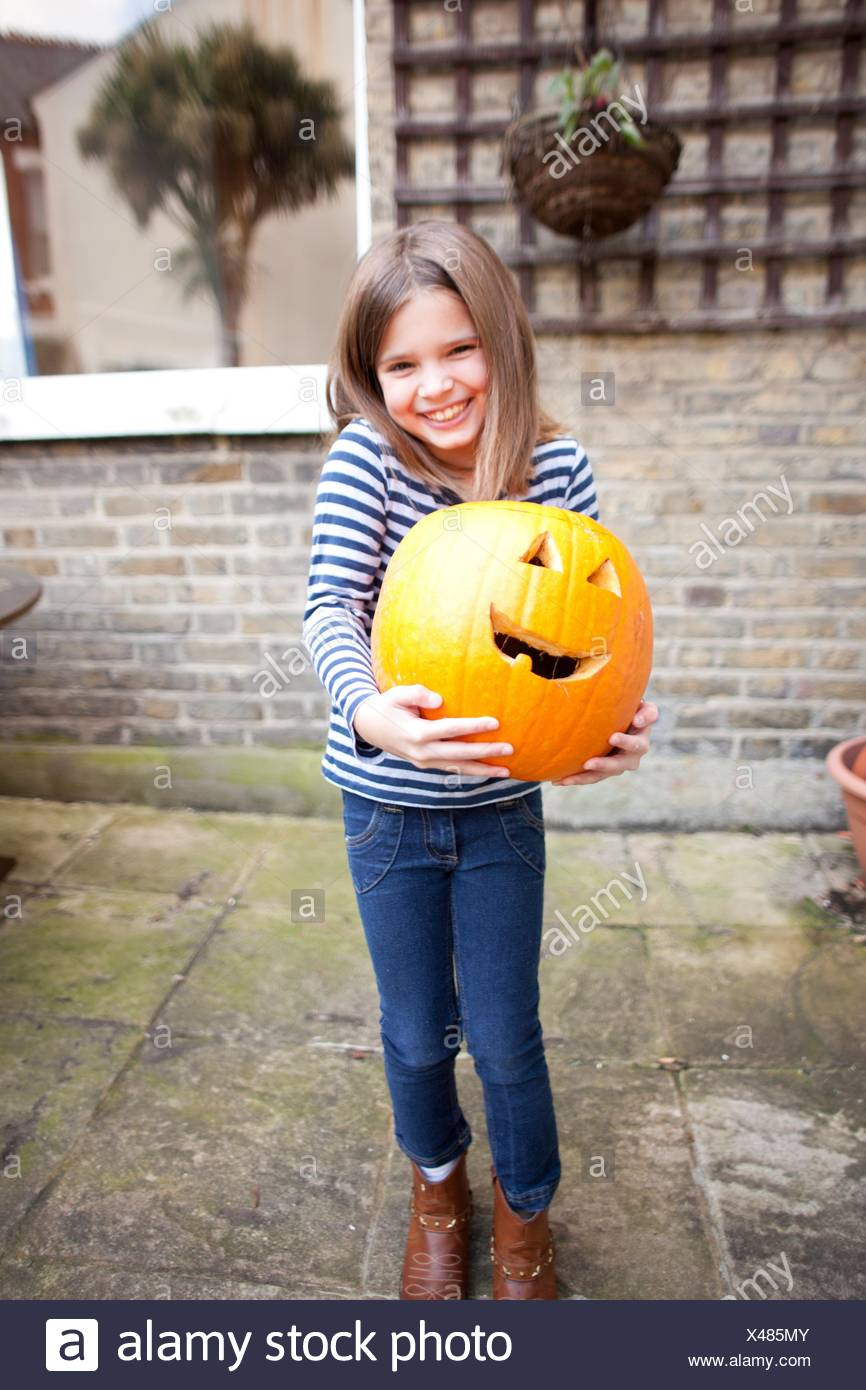 Smiling girl holding heavy halloween pumpkin in garden - Stock Image