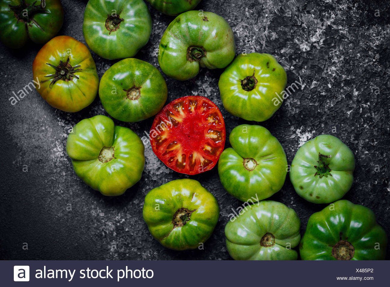 Green heirloom tomatoes gathered on a board and one halved red tomato is in the center. - Stock Image
