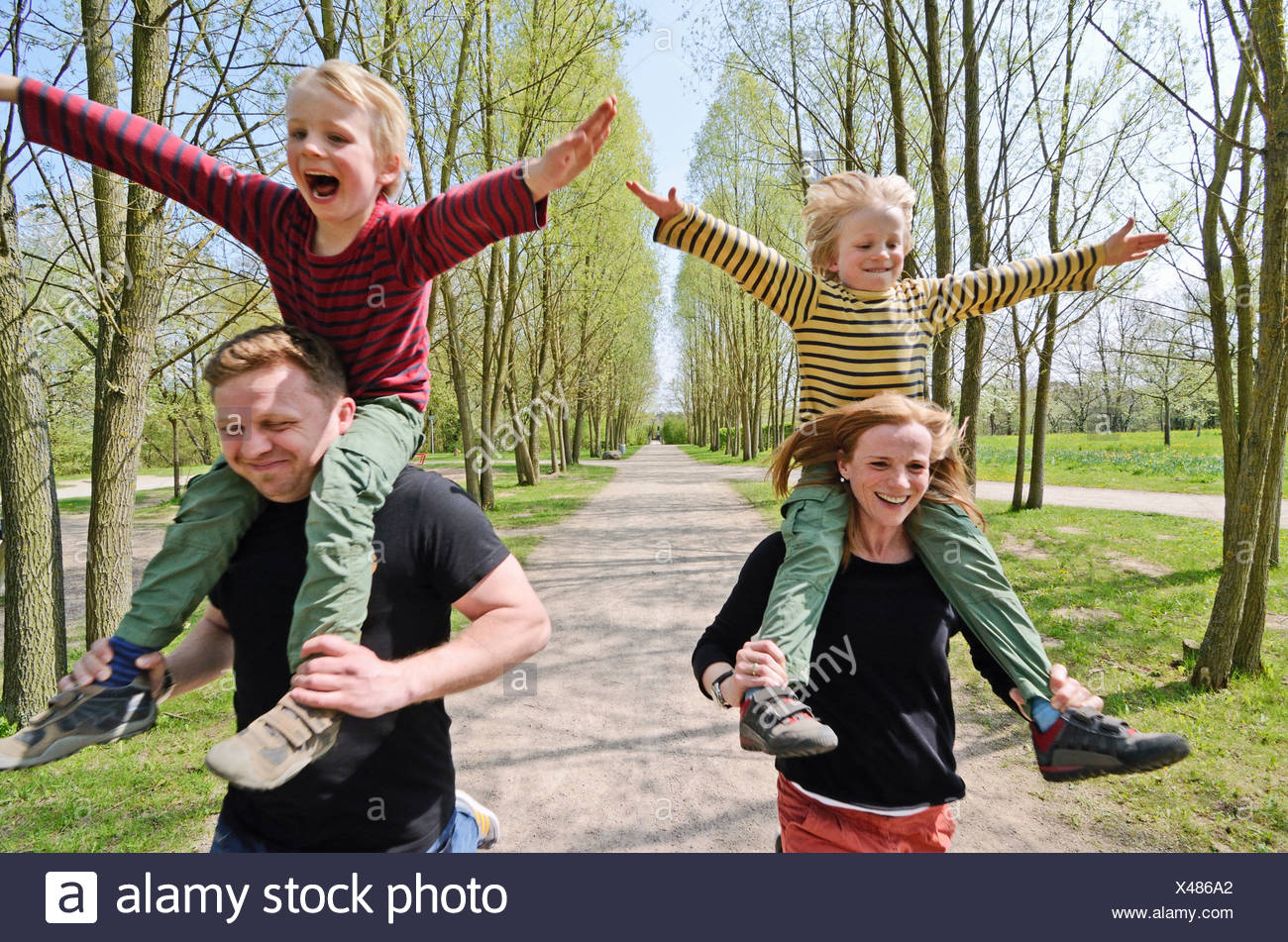 Mother and father racing with two boys on shoulders through park - Stock Image