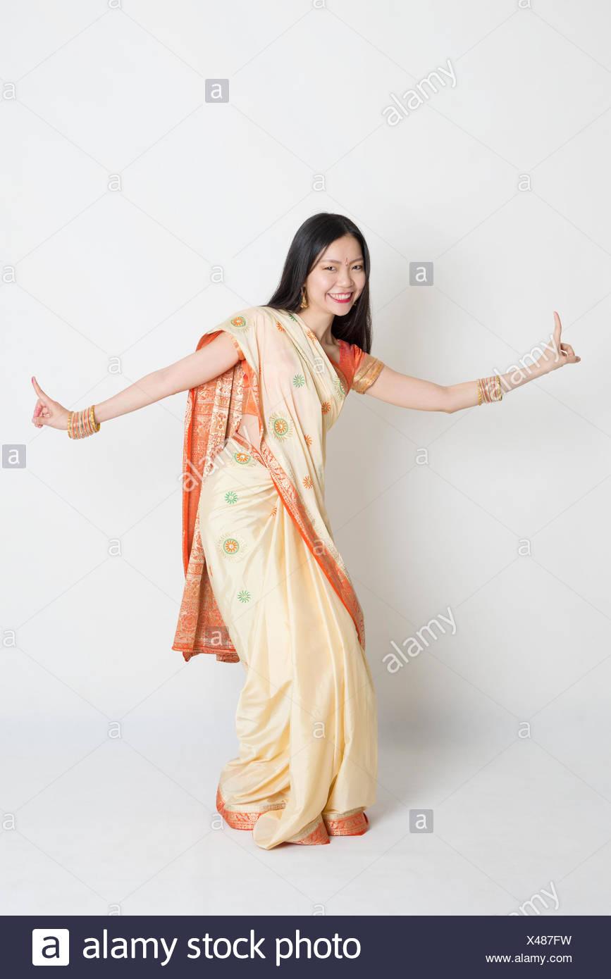 Female in Indian sari dress dancing - Stock Image