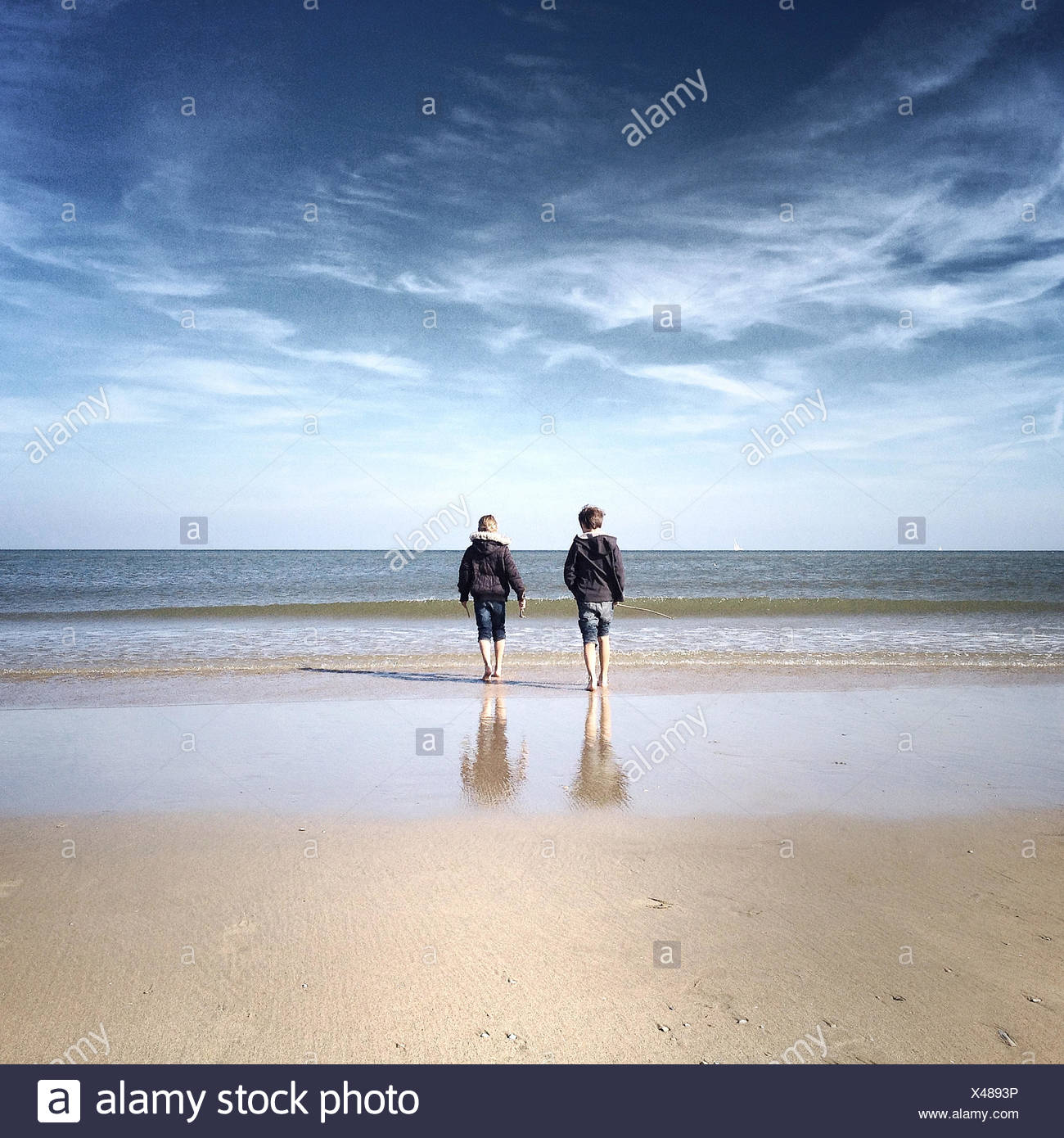 Rear view of two children on beach - Stock Image