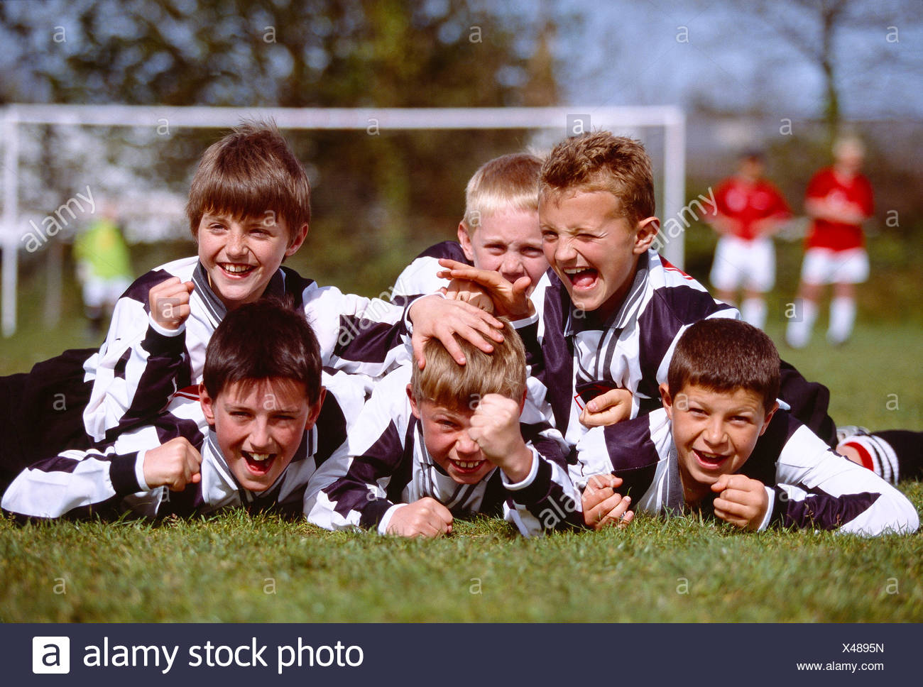Children. Sport. Group of happy boys celebrating victory at end of Soccer game. - Stock Image