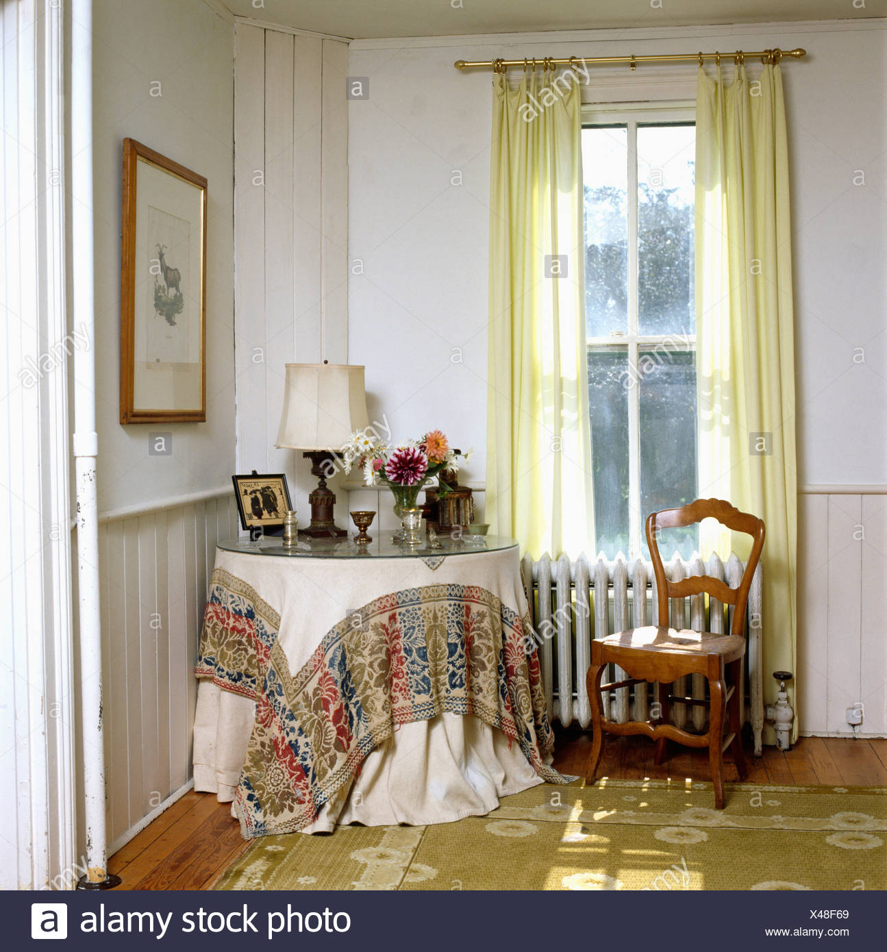 Cloth With Patterned Hem On Circular Table In Corner Of Sitting Room With Yellow Drapes At Tall Window Stock Photo Alamy