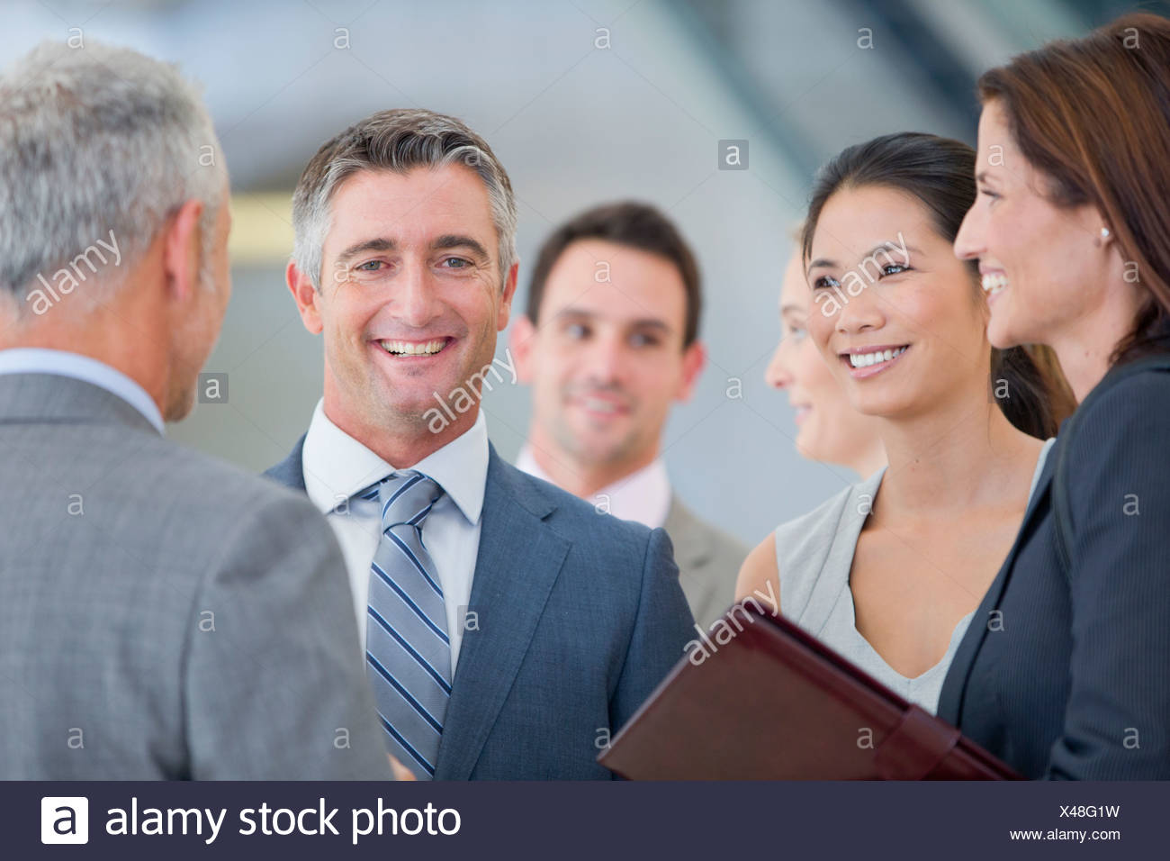 Portrait of smiling businessman among co-workers Stock Photo