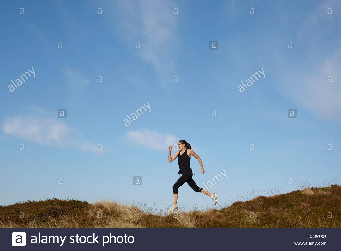 Woman running on rural hillside Stock Photo
