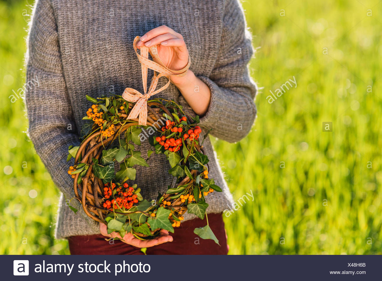 Woman holding autumnal wreath, detail, - Stock Image