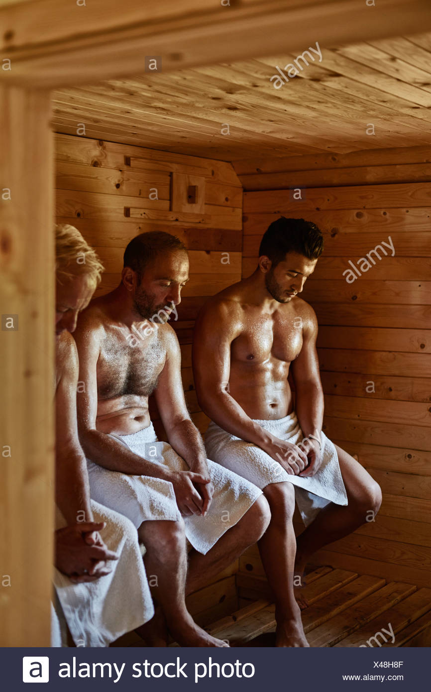 Three men sitting in sauna with heads down - Stock Image