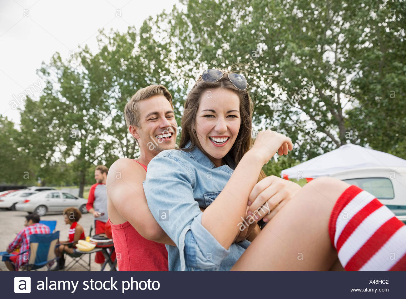 Man carrying girlfriend at tailgate barbecue in field - Stock Image