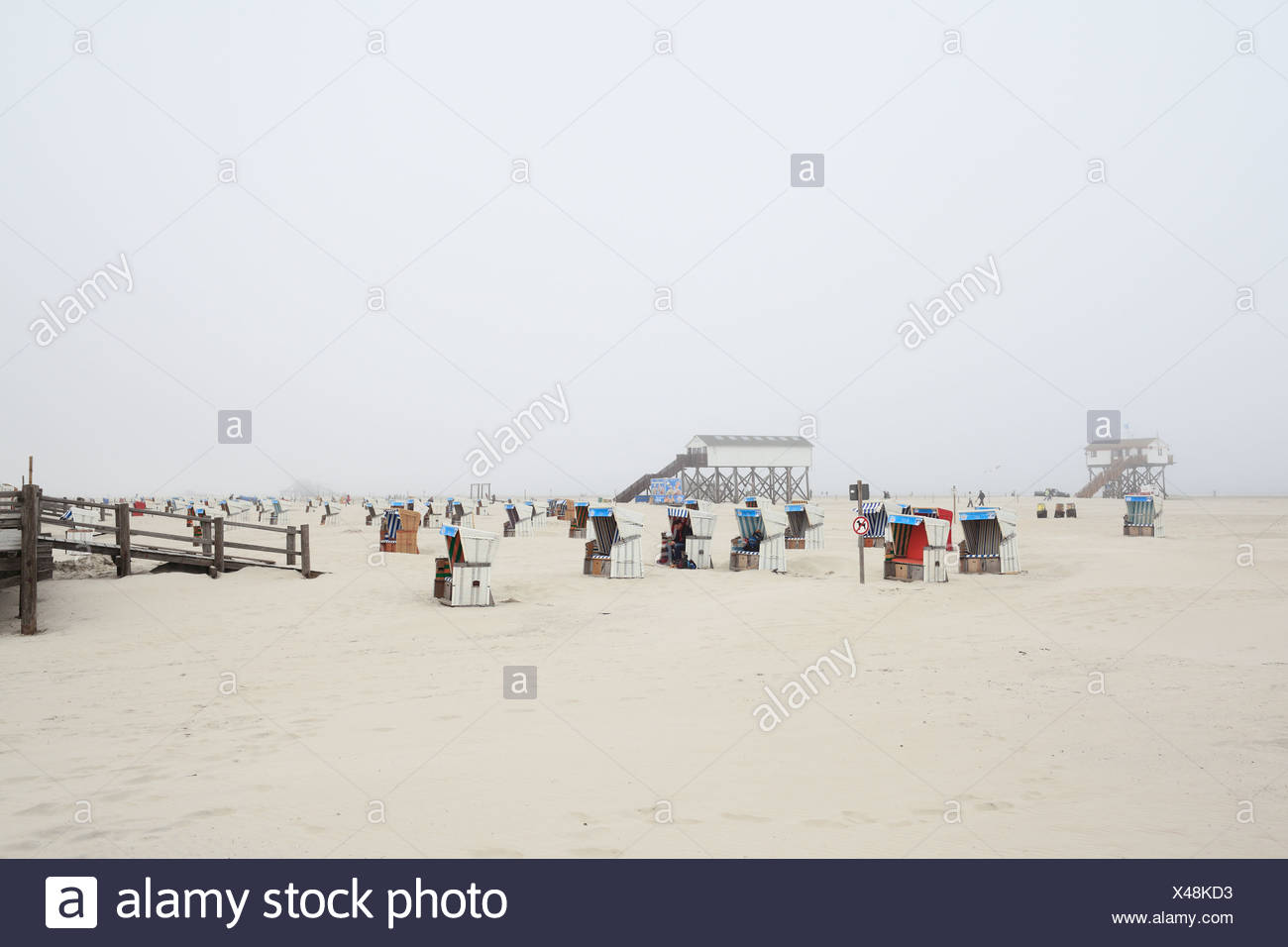 Sankt Peter-Ording, Germany, and Strandkoerbe stilts in fog at the beach - Stock Image