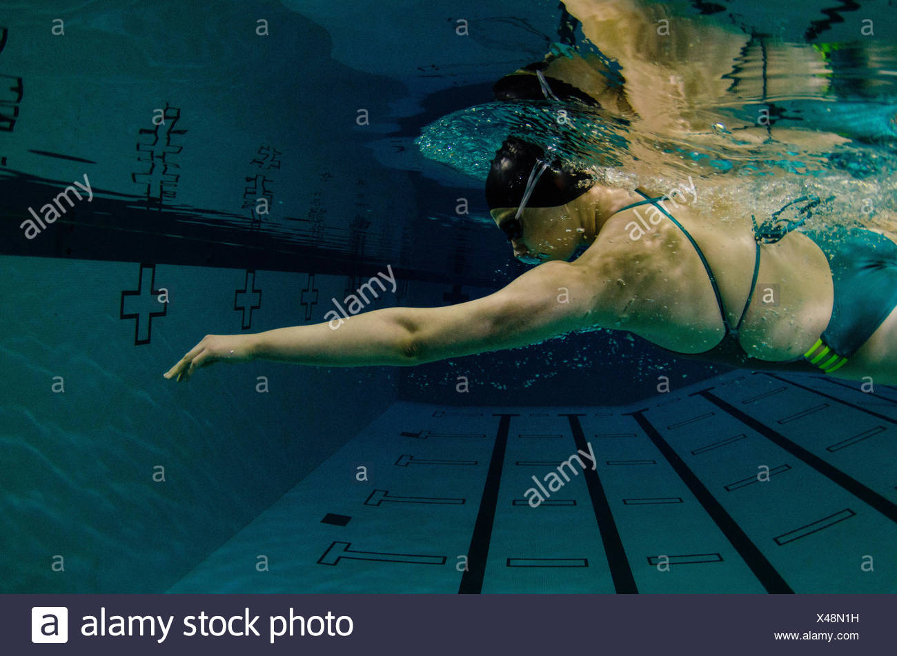 A young woman in a green bathing suit, black swim cap, and goggles, swims freestyle. - Stock Image