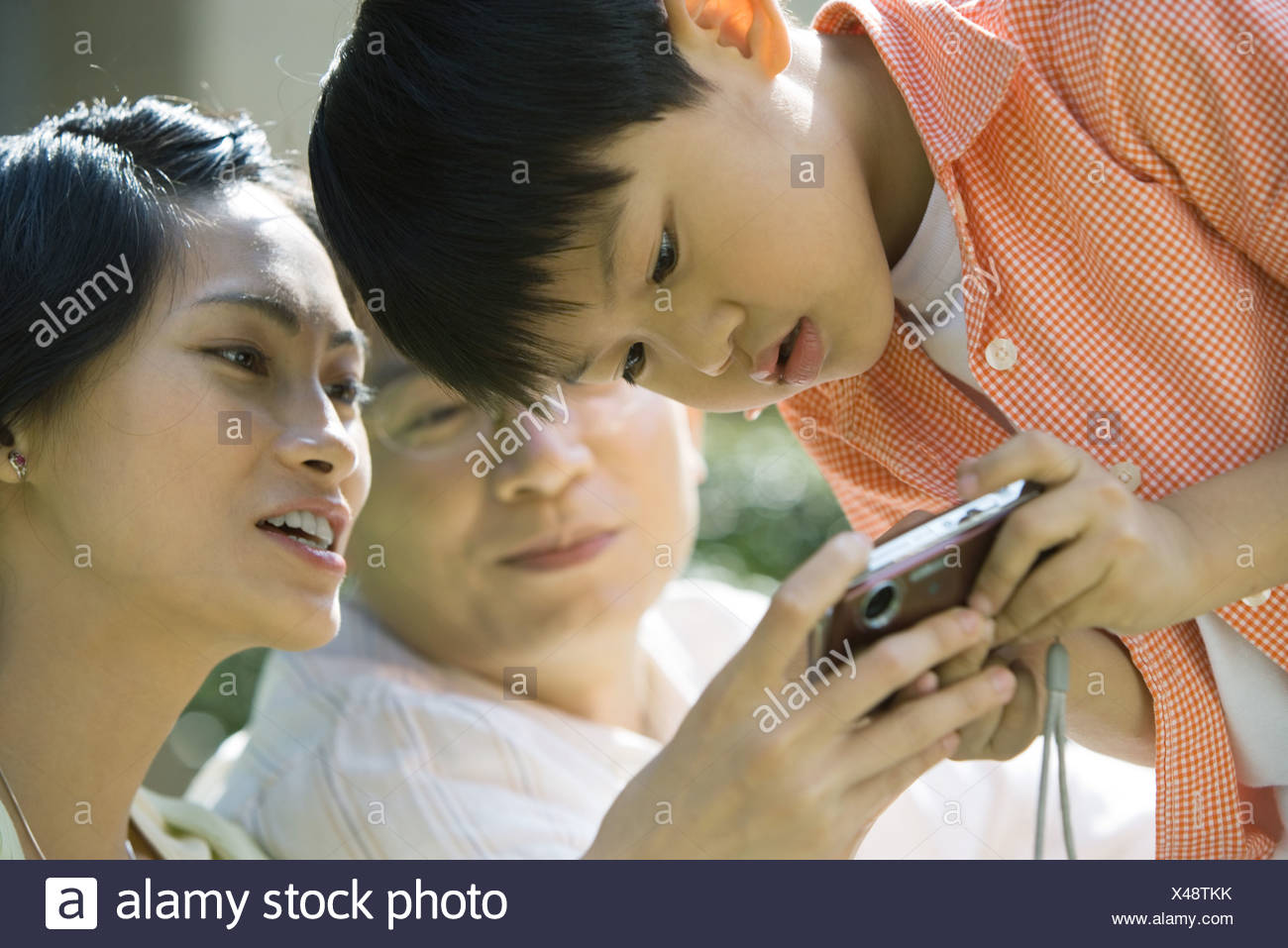 Boy with parents, mother holding digital camera, boy bending over to look - Stock Image