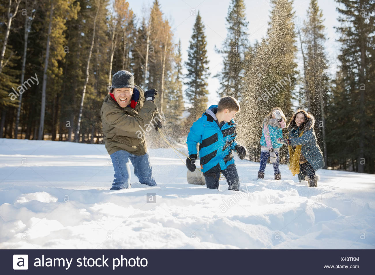 Playful family having snowball fight - Stock Image