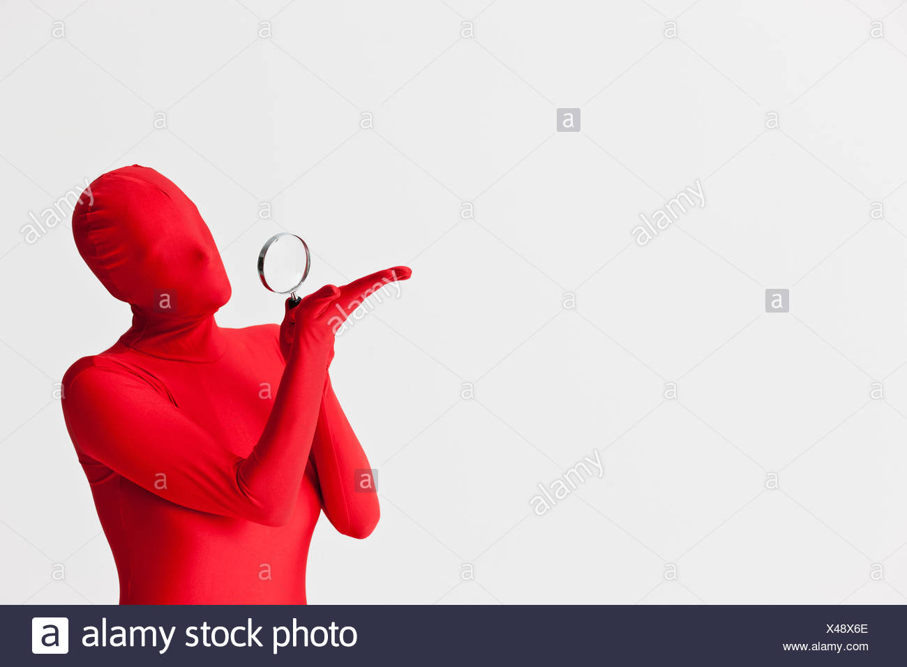Woman in bodysuit with magnifying glass - Stock Image
