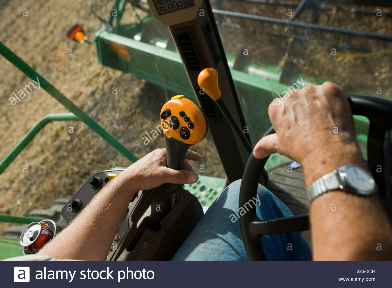 Agriculture - The hands of a farmer operating the controls of a combine during the soybean harvest / Northland, Minnesota, USA. - Stock Image