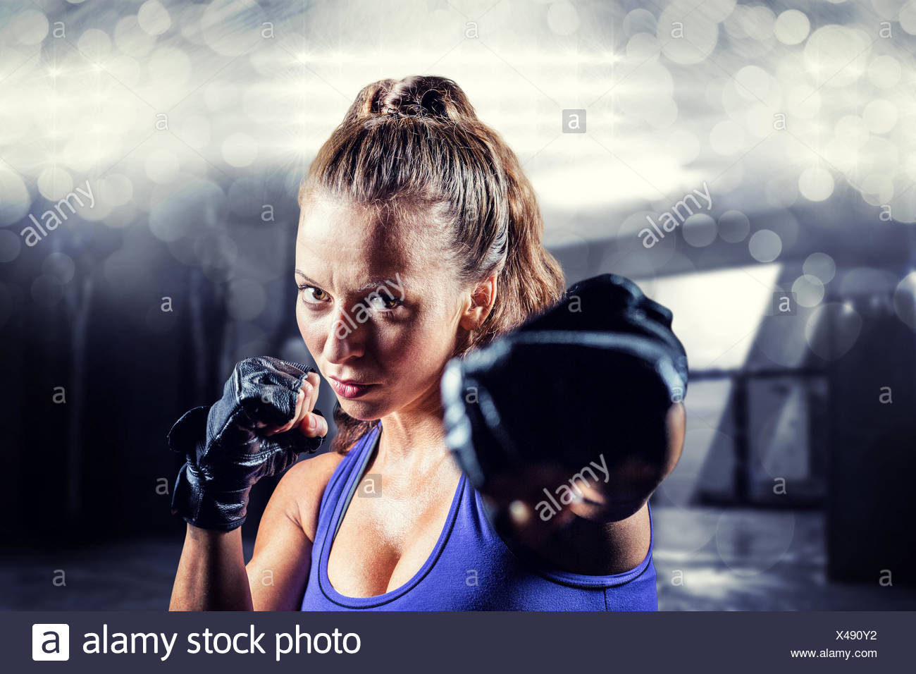 Composite image of portrait of female fighter punching - Stock Image
