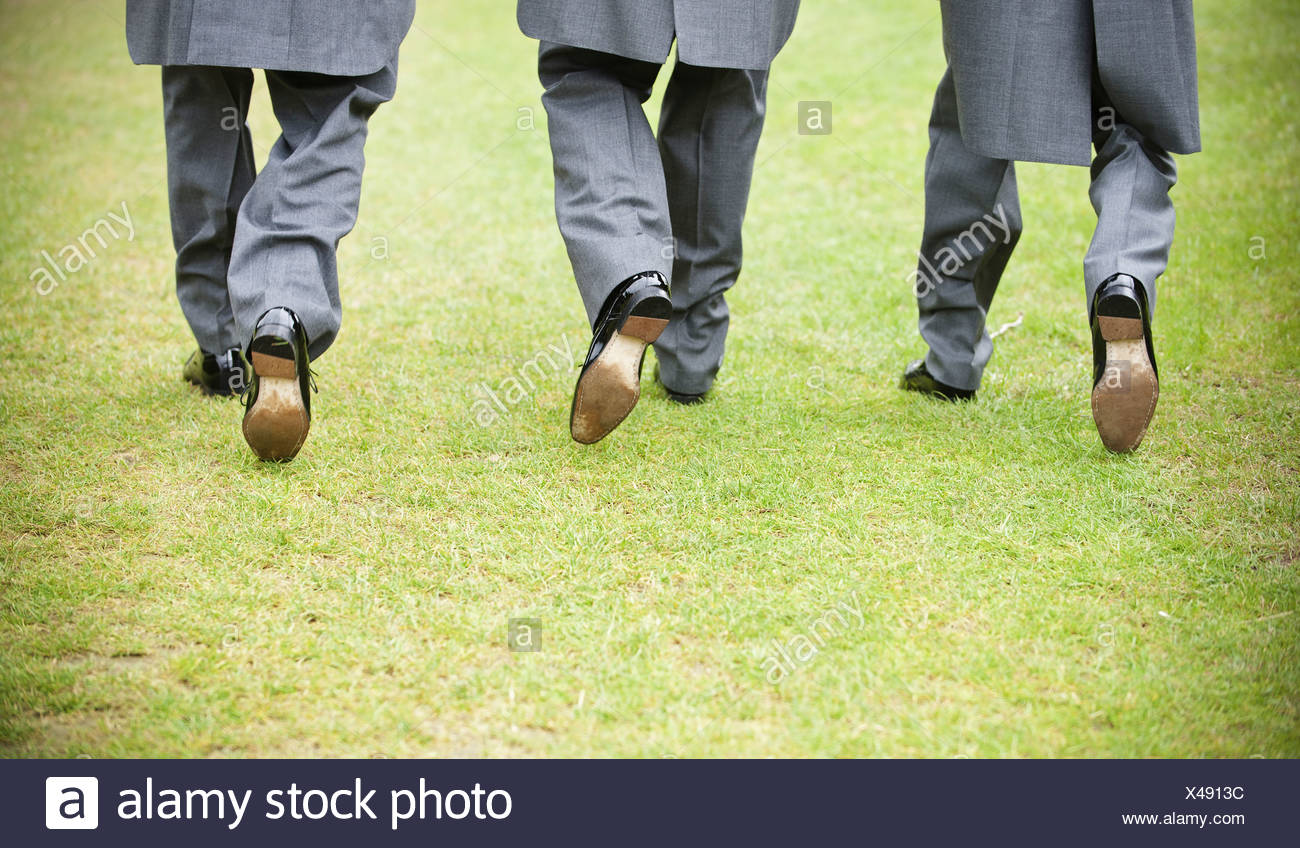 Groom and two best man in black shoes grey trousers and morning coats walking along a lawn Back view  England Stock Photo