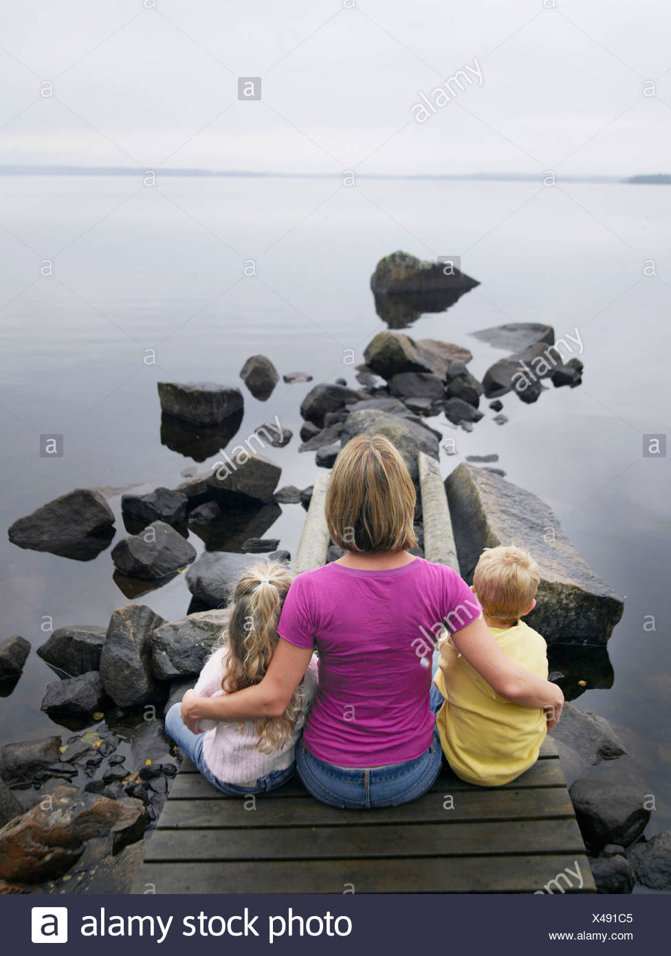 Woman with young boy and young girl sitting on a dock by a lake. Stock Photo