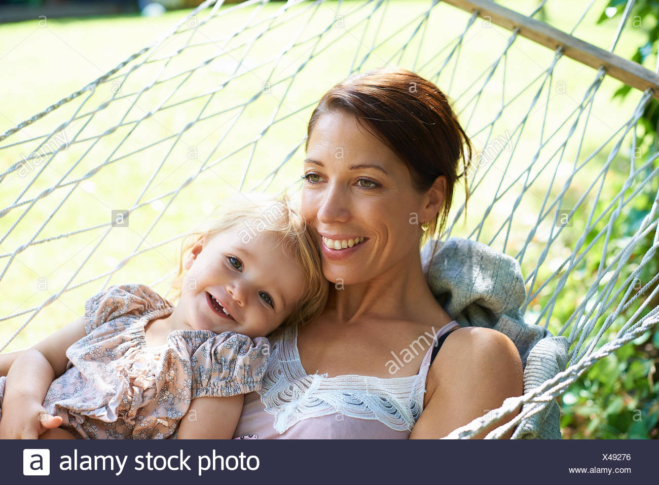 Mid adult mother and toddler daughter reclining in garden hammock - Stock Image