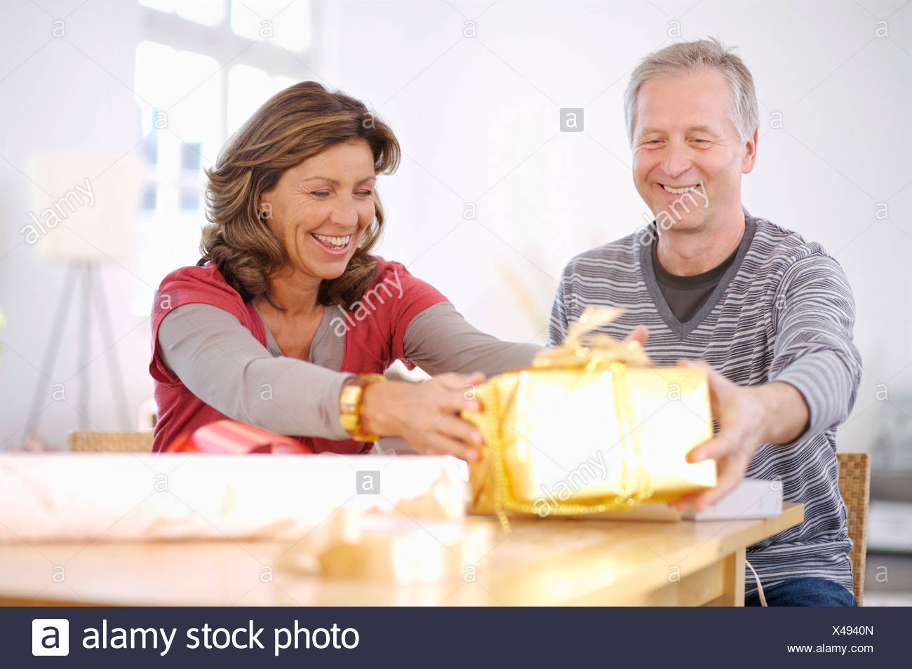 Mature couple holding shiny gift at table - Stock Image