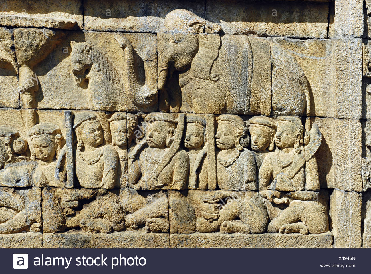 Indonesia-Java, Borobudur, Warriors seated cross-legged with sword and  stalk on their shoulder, behind them is the depiction of