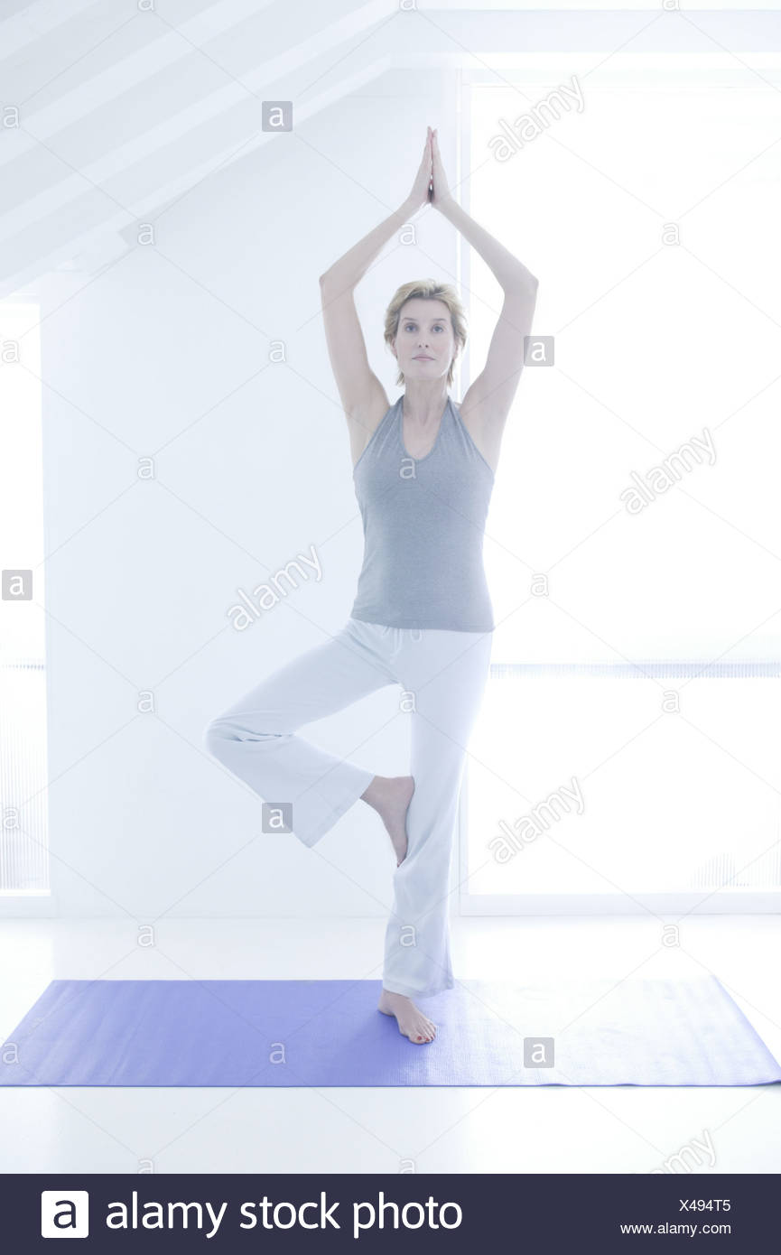 A woman standing in a yoga pose - Stock Image