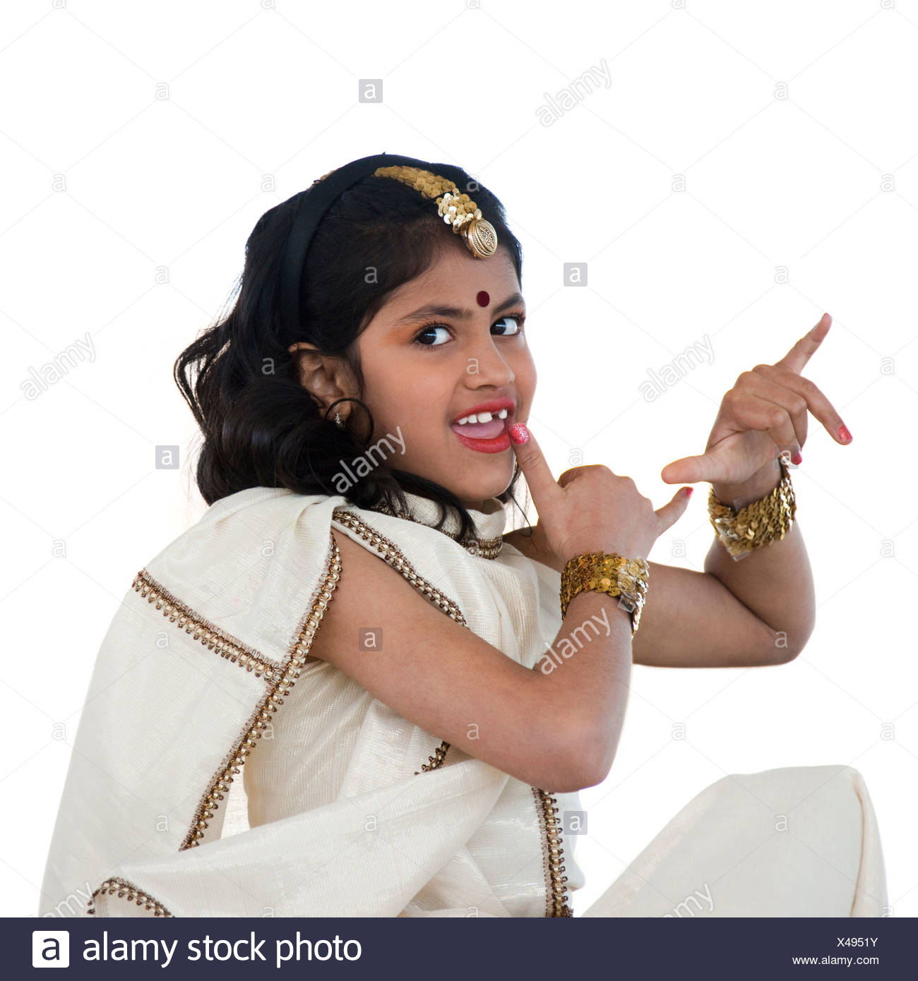Girl (8-9) wearing traditional sari performing figures from indian traditional dance, studio shot - Stock Image