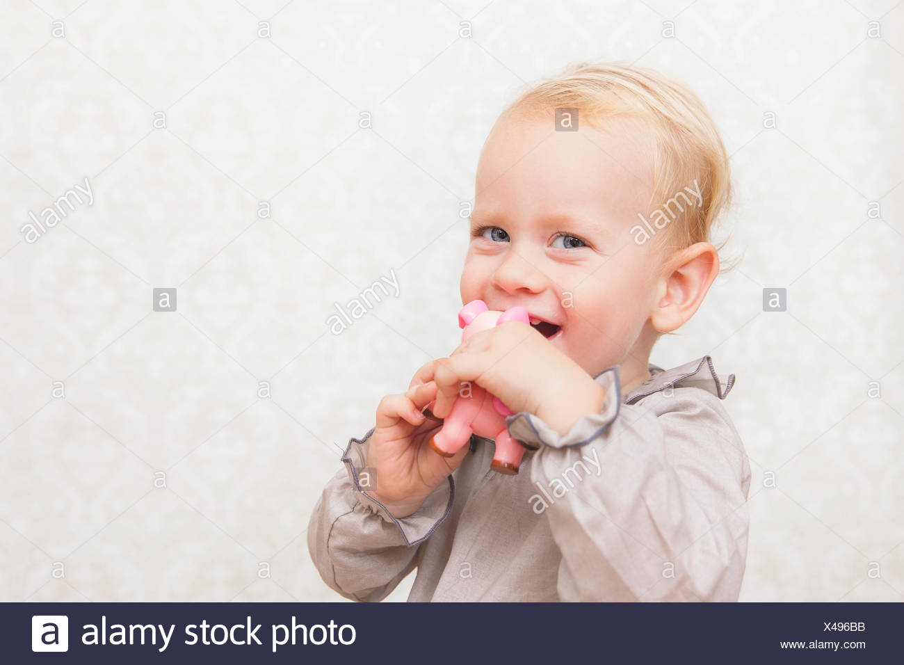 Portrait of a smiling boy holding a pink toy - Stock Image
