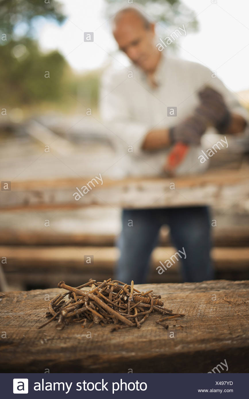 A man working in a reclaimed timber yard remove metals from piece of timber A heap of rusty metal nails - Stock Image