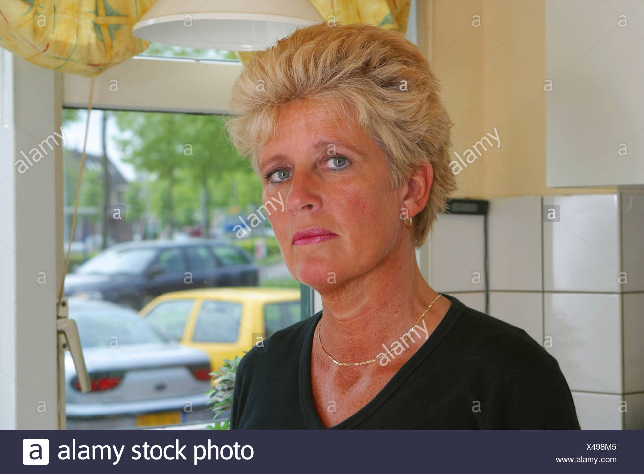 Unhappy mid aged woman in kitchen headshot - Stock Image