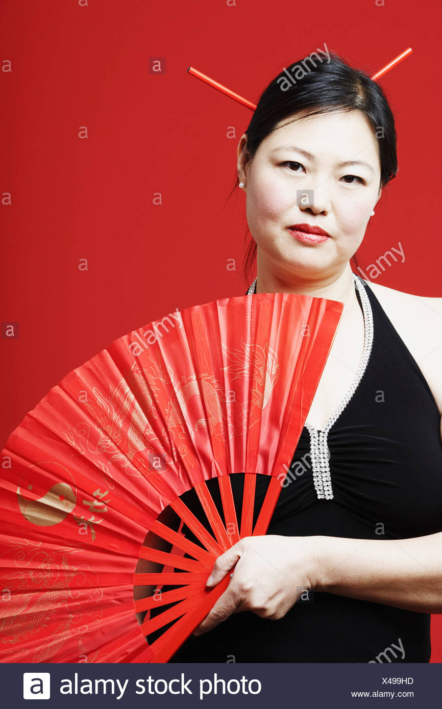 Portrait of a mid adult woman holding a folding fan - Stock Image