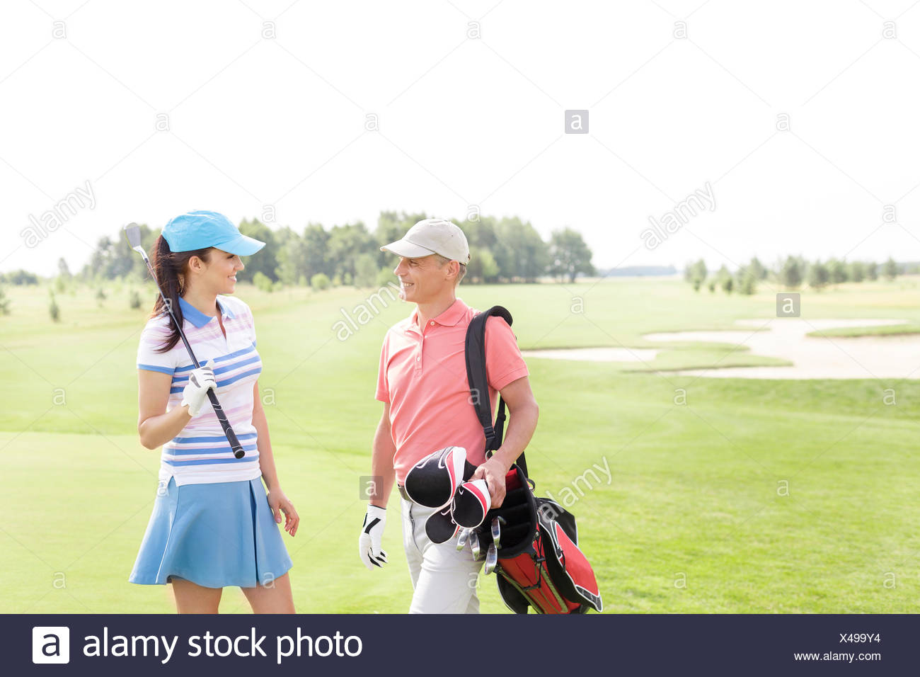 Male and female golfers communicating at golf course Stock Photo