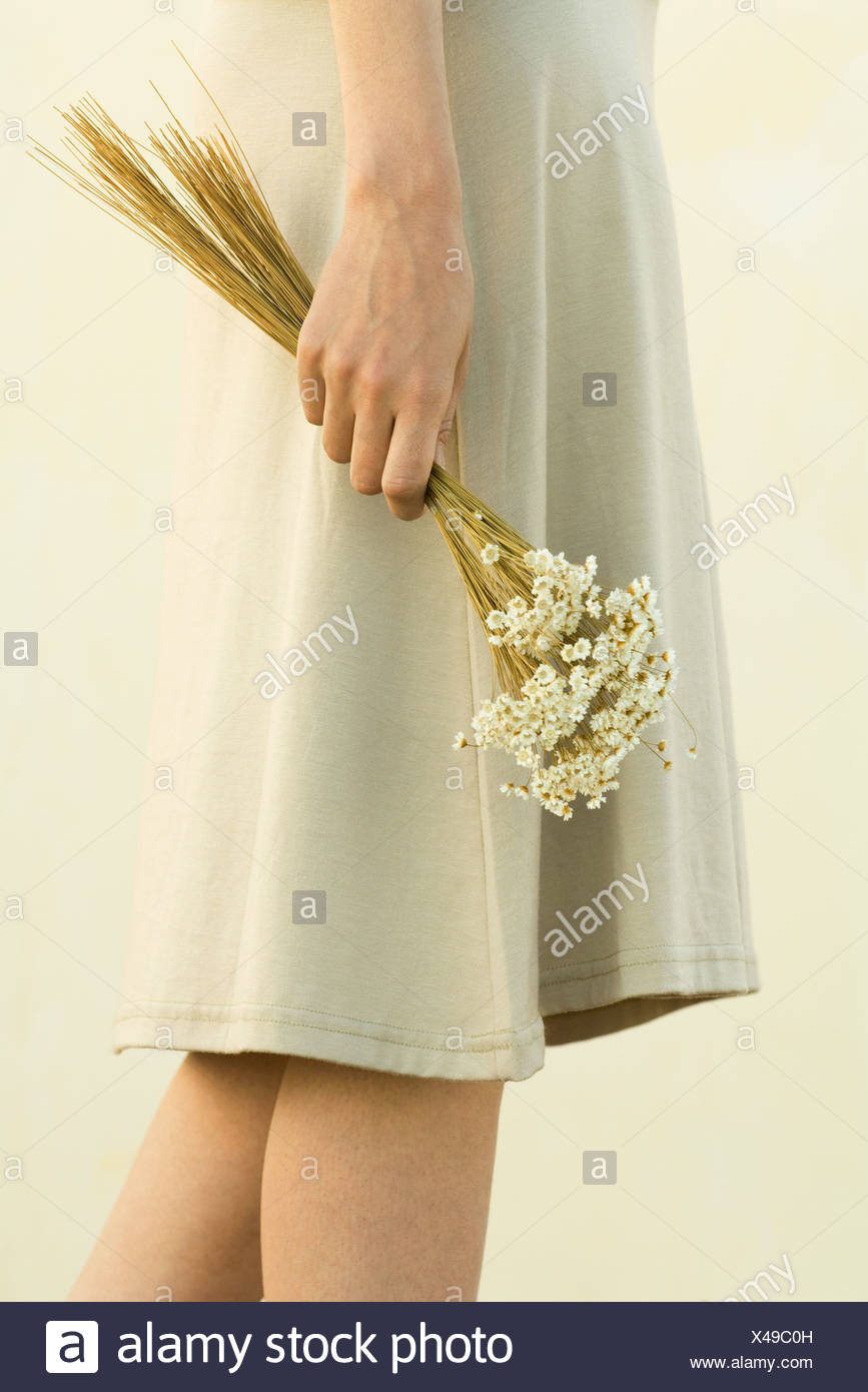 Woman walking, holding bouquet of tiny white flowers, cropped view - Stock Image