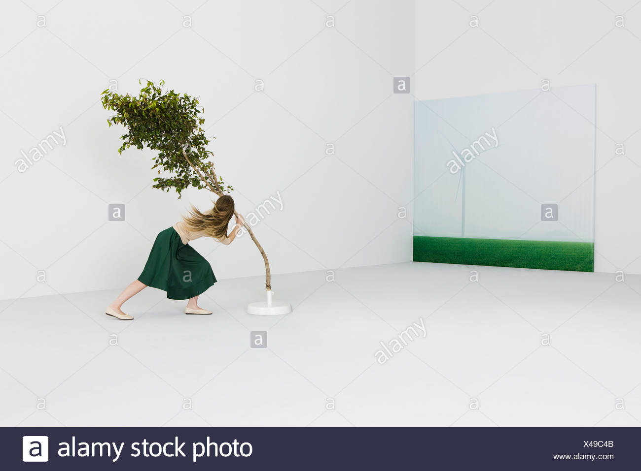 Woman struggling against strong wind, holding on to leaning tree, wind turbine in background - Stock Image