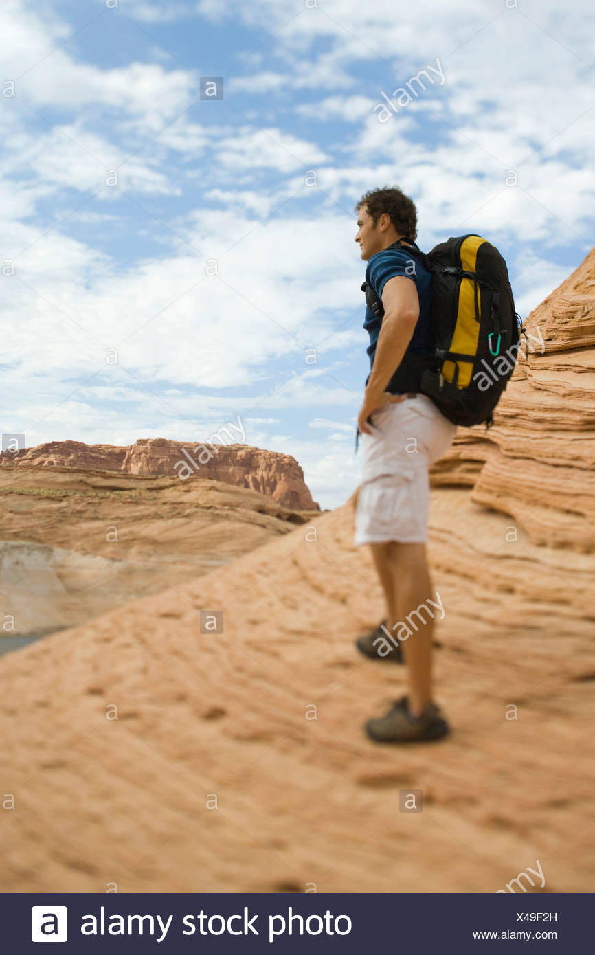 Man with backpack taking photo - Stock Image