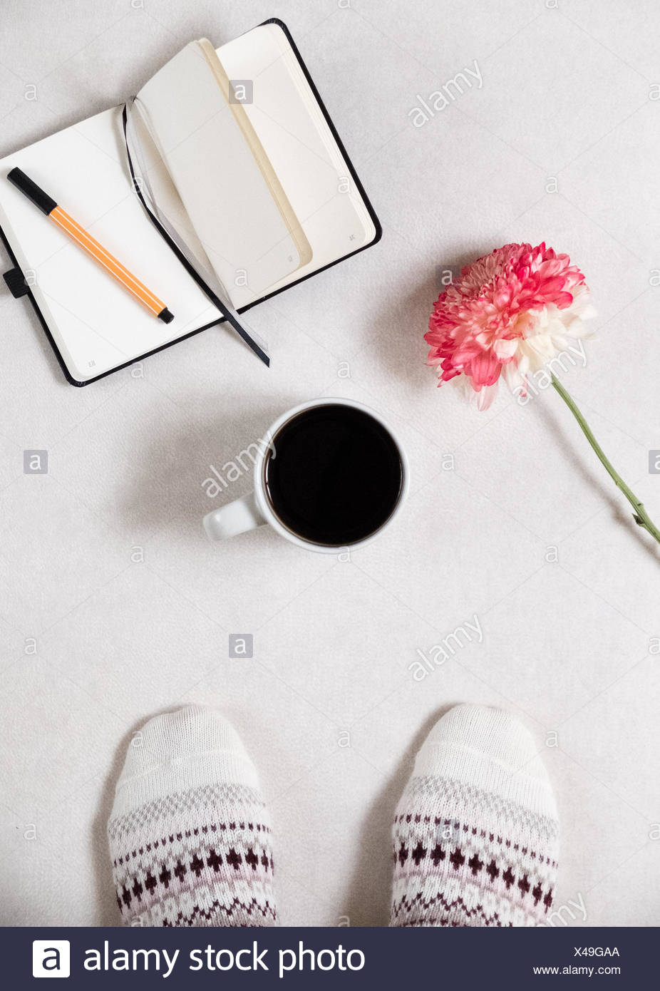 Low Section Of Person Standing By Black Coffee And Diary With Pen On White Background - Stock Image