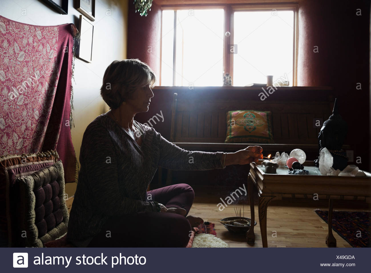 Senior woman lighting incense in meditation room - Stock Image