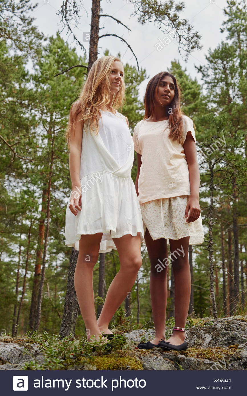 Portrait of teenage girls standing on rocks in forest - Stock Image