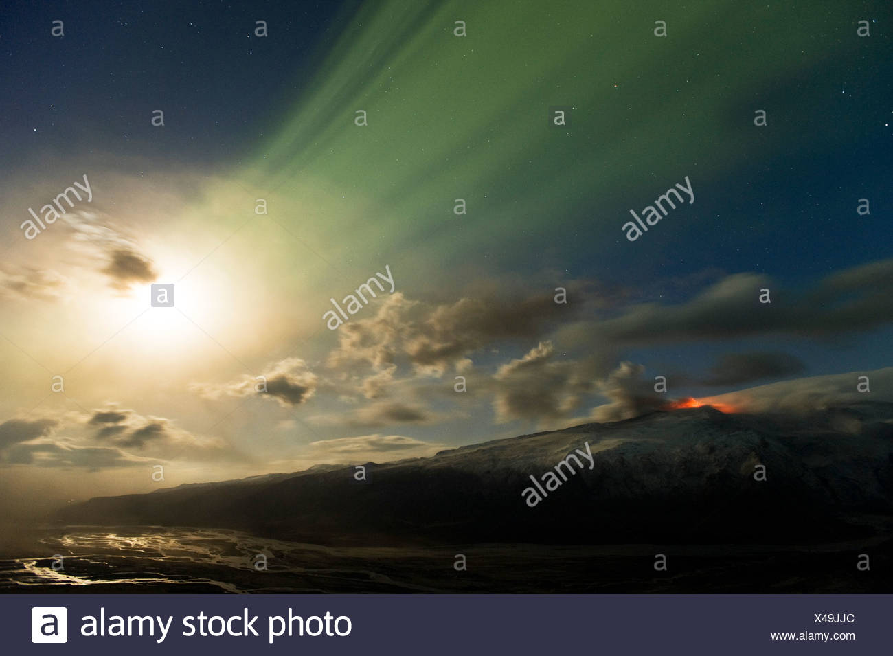 Weak northern lights and full moon over the final eruption of Eyjafjallajoekull Volcano and the river bed of the Markarfljót - Stock Image