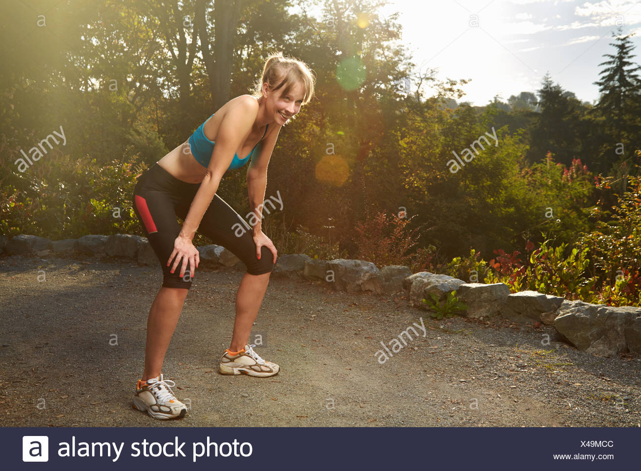 Exhausted female runner taking a break in park - Stock Image
