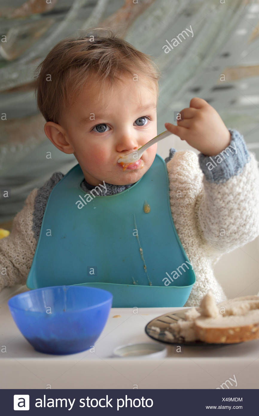 Portrait of baby boy (18-23 months) wearing baby bib eating at table - Stock Image