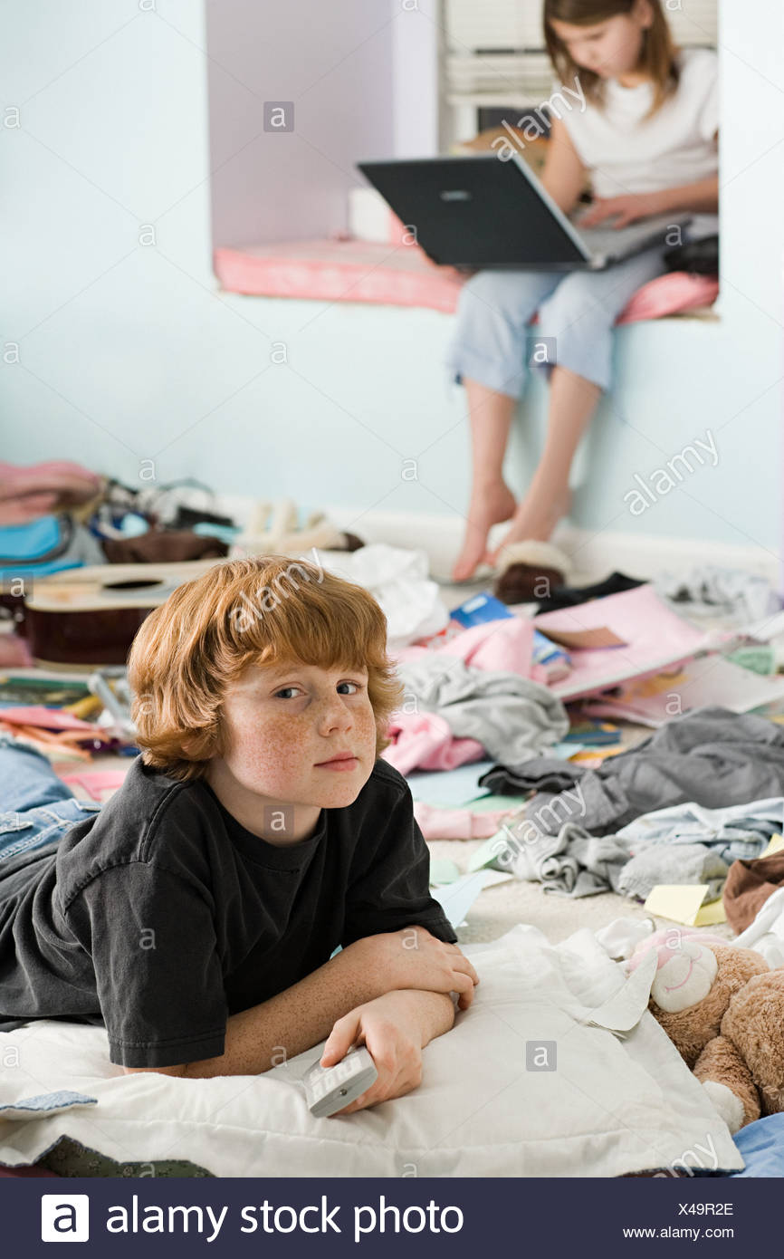 A boy and girl in a messy bedroom - Stock Image