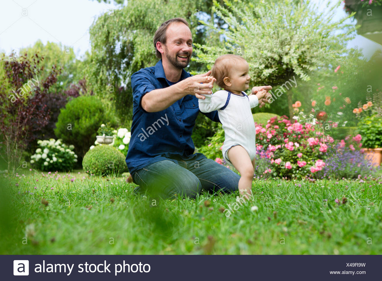 Father holding baby daughters hands whilst toddling in garden - Stock Image