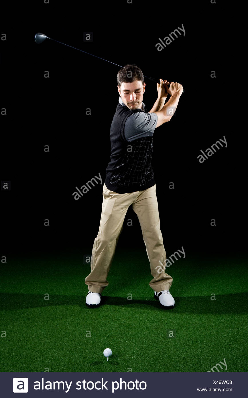 A golfer teeing off, portrait, studio shot - Stock Image