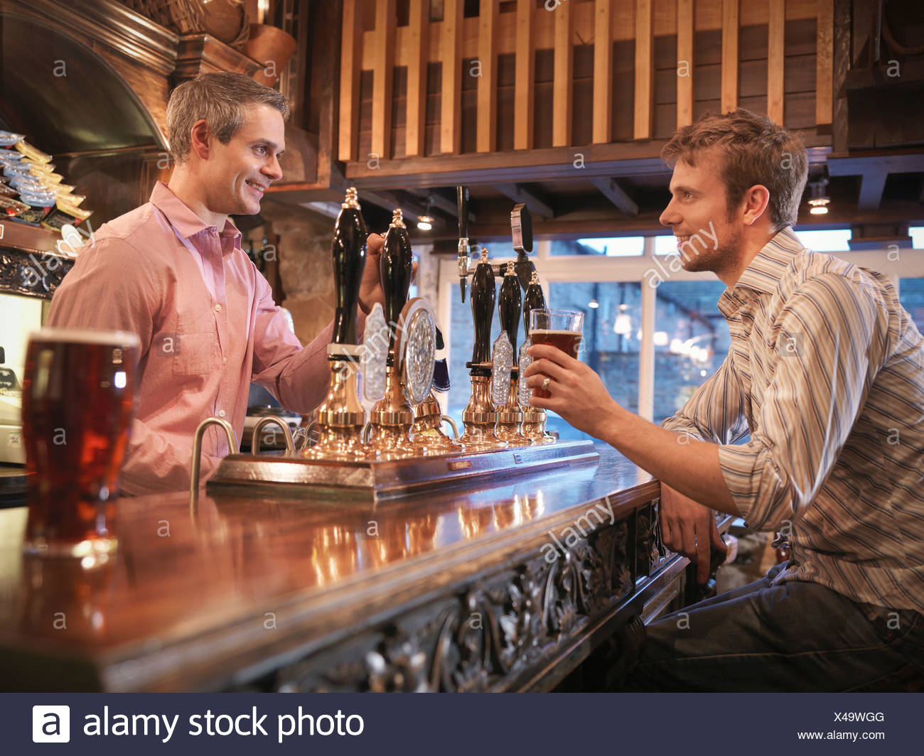 Landlord and customer in English pub - Stock Image