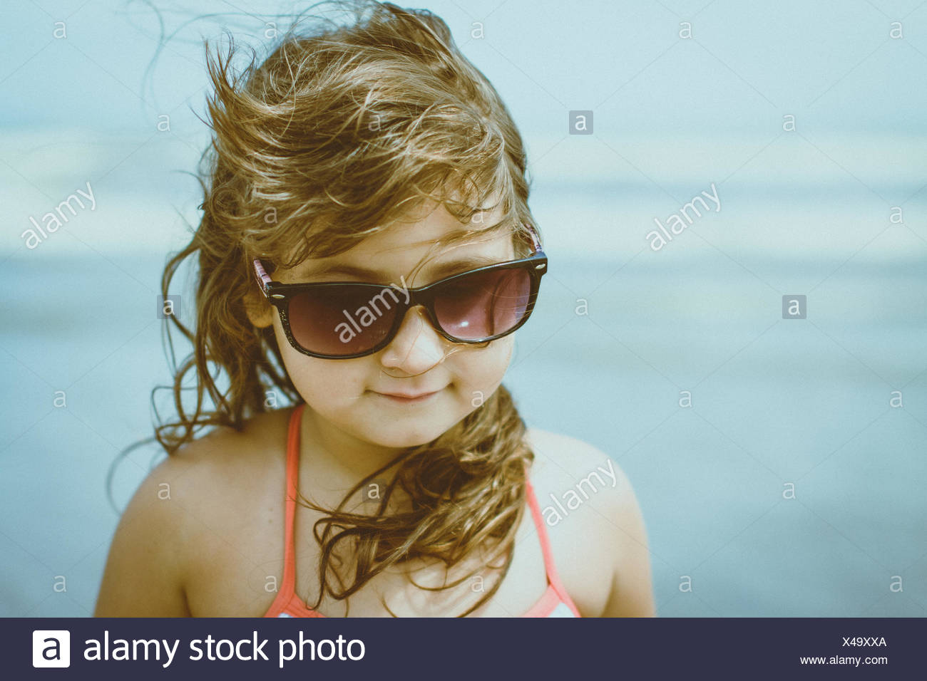 Portrait of girl (4-5) with windswept blonde hair wearing sunglasses - Stock Image