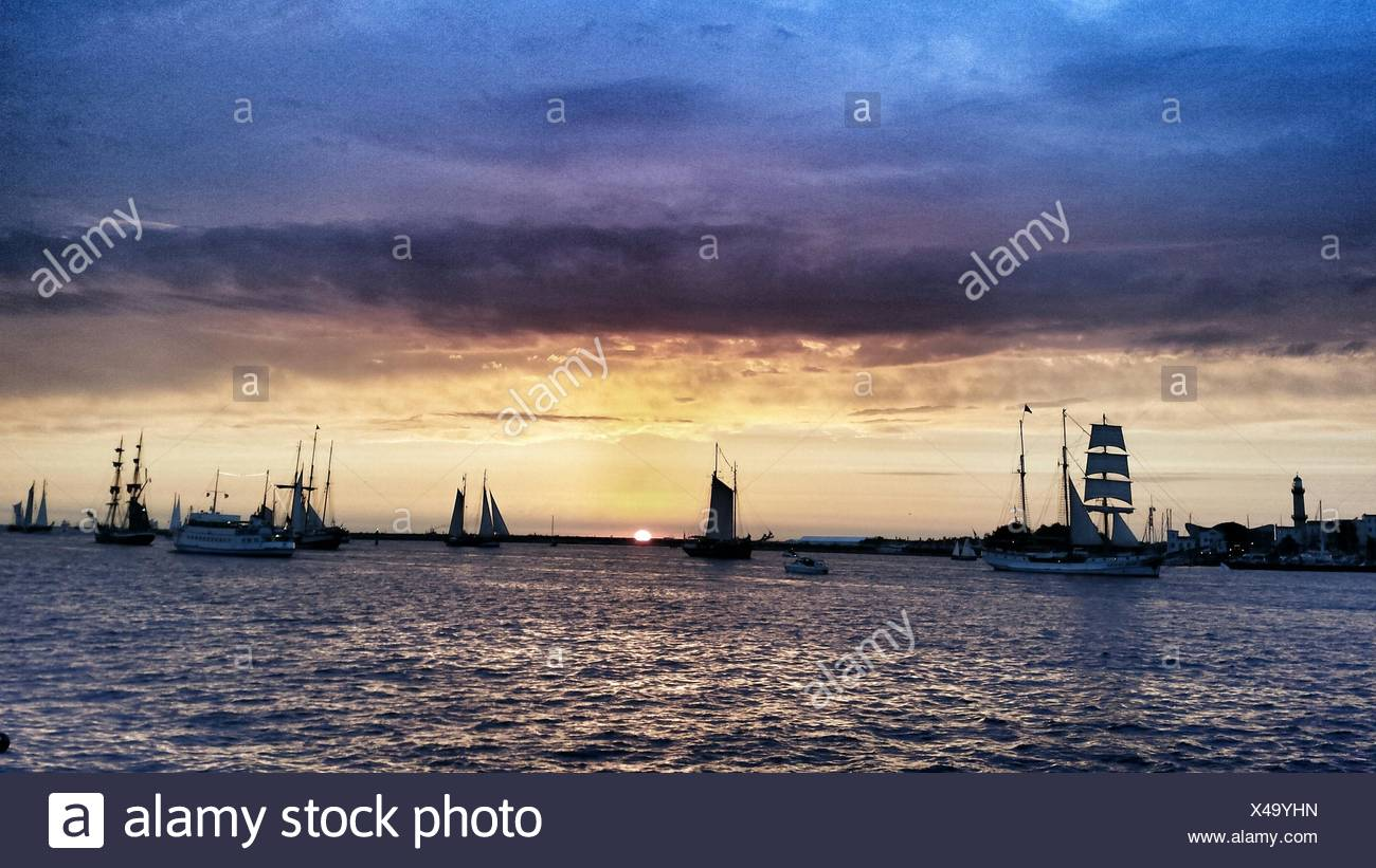 Sailboats In Sea Against Sunset Sky During Hanse Sail At Rostock - Stock Image