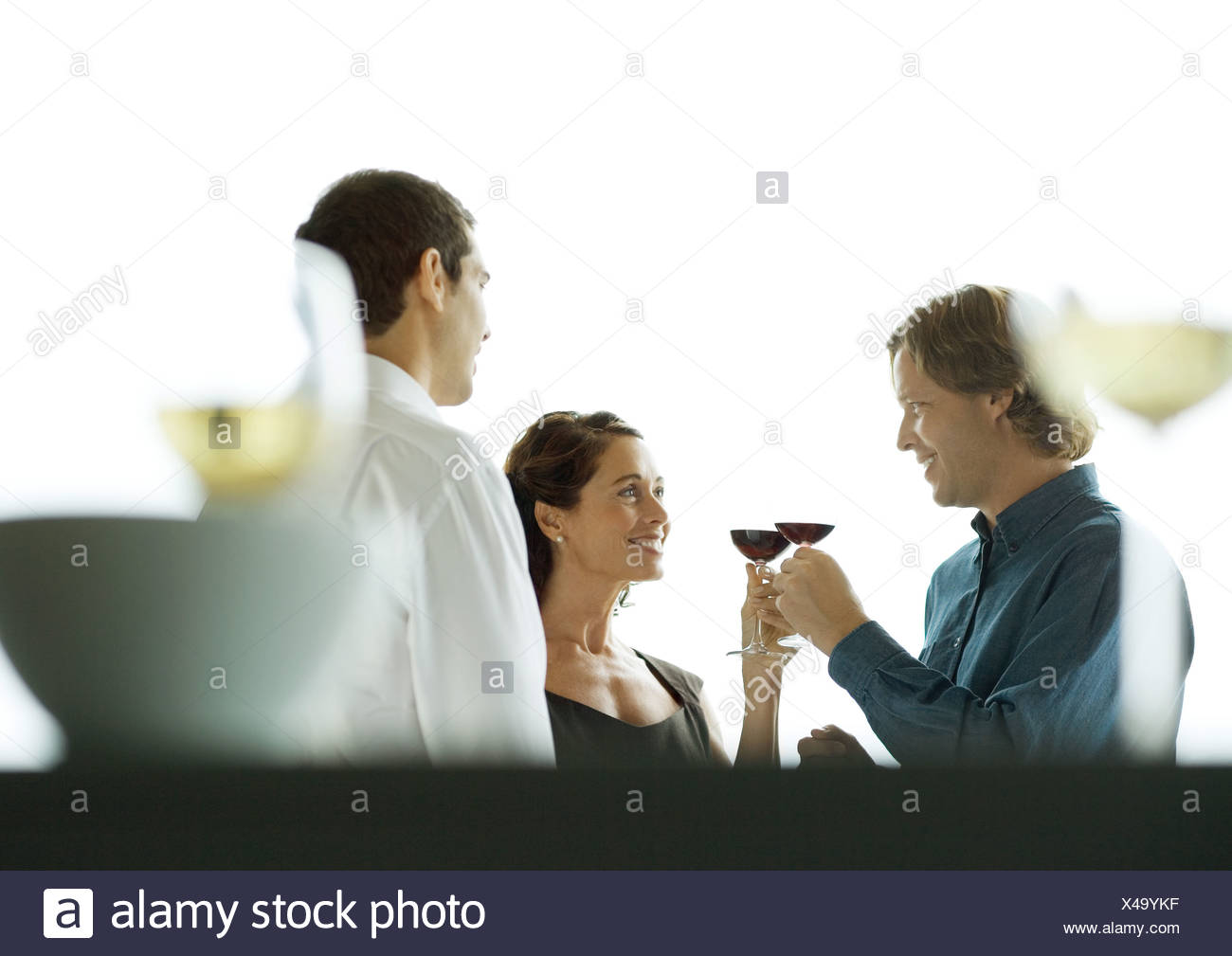 Man and woman clinking glasses during party - Stock Image