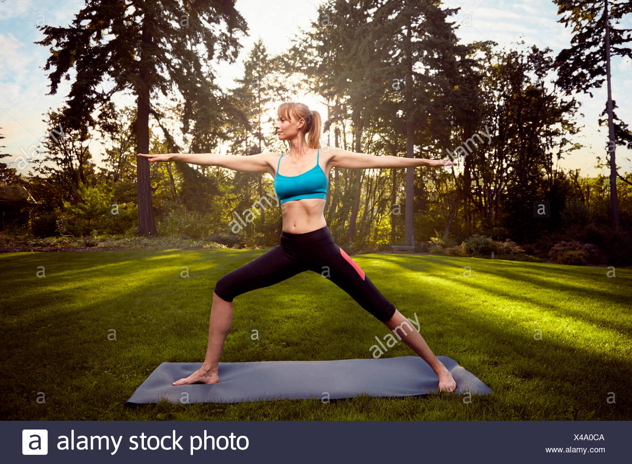Mid adult woman practicing warrior pose in park - Stock Image
